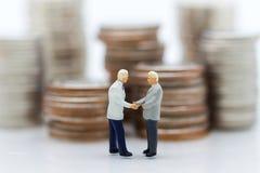 Personnes miniatures : Deux hommes d'affaires font une affaire, avec la pile de pièces de monnaie au fond, Photographie stock libre de droits
