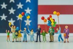 Personnes miniatures, famille américaine heureuse tenant le ballon avec Uni Image libre de droits