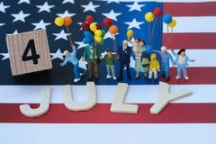 personnes miniatures, famille américaine heureuse tenant le ballon et le bois Photo stock