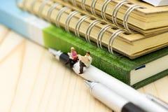 Personnes miniatures : Homme d'affaires s'asseyant sur le stylo et le journal lu Utilisation d'image pour l'éducation de fond, ou Photo libre de droits