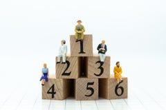 Personnes miniatures : Homme d'affaires s'asseyant sur les blocs en bois avec des nombres séquentiels Utilisation d'image pour le Photo stock