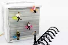Personnes miniatures : journal de lecture d'homme d'affaires sur un grand livre Utilisation d'image pour l'éducation de fond ou l Photo stock