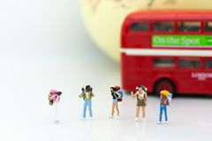 Personnes miniatures : l'autobus de attente de randonneur à la gare routière pour vont au plan de destination Utilisation d'image Image stock