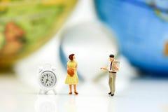Personnes miniatures : Les couples de l'amour se tiennent avec la carte d'horloge et du monde Photos stock