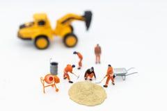 Personnes miniatures : Les travailleurs de la construction établissant des plans, ont des matériaux de construction, sable, briqu image stock