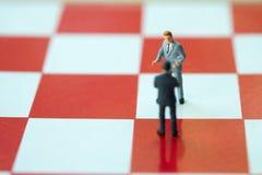 Personnes miniatures : Poign?e de main d'homme d'affaires ? la r?ussite commerciale sur l'?chiquier image stock