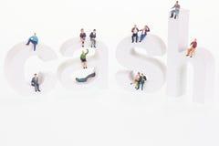 Personnes miniatures s'asseyant sur les lettres en bois d'argent liquide photographie stock libre de droits