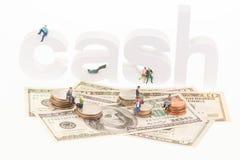 Personnes miniatures s'asseyant sur les lettres et les pièces de monnaie en bois d'argent liquide Photographie stock