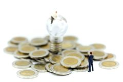 Personnes miniatures : Support d'homme d'affaires avec des pièces de monnaie et l'idée de lampe, Bu Images libres de droits
