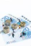Personnes miniatures sur 20 euro billets de banque et fin de vue supérieure de pièces de monnaie  Images libres de droits