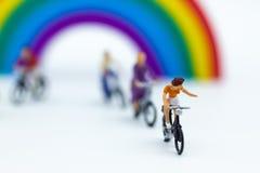 Personnes miniatures : Touriste faisant un cycle la bicyclette le long de l'arc-en-ciel Utilisation d'image pour le concept de vo Images libres de droits