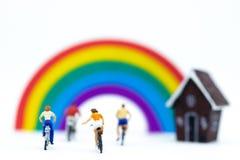 Personnes miniatures : Touriste faisant un cycle la bicyclette le long de l'arc-en-ciel Utilisation d'image pour le concept de vo Images stock