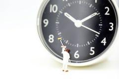 Personnes miniatures : travailleur nettoyant une horloge, concept de temps Images stock