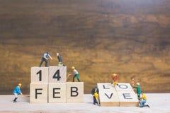 Personnes miniatures : Travailleur renforcement d'équipe mot ` ` du 14 février sur le bloc en bois Image stock