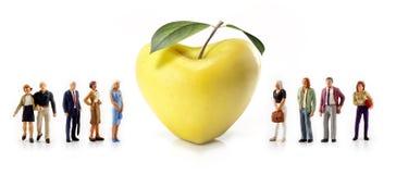 Personnes miniatures - un groupe de personnes posent à côté d'une pomme en forme de coeur jaune Images stock
