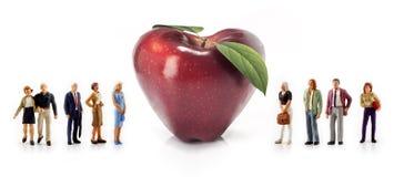 Personnes miniatures - un groupe de personnes posent à côté d'une pomme en forme de coeur rouge Photo libre de droits