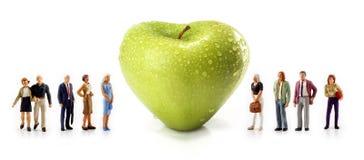 Personnes miniatures - un groupe de personnes posent à côté d'une pomme en forme de coeur verte Photographie stock libre de droits