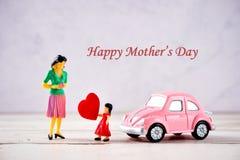 Personnes miniatures : Une mère qui est donnée un coeur dans l'amour par la fille de petit enfant avec peu de voiture de rose de  Images libres de droits