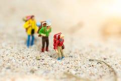 Personnes miniatures : voyageurs avec le sac à dos marchant sur la plage Utilisation d'image pour le voyage, concept de vacances Image libre de droits
