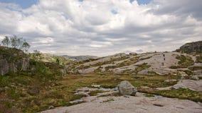 Personnes minuscules trimardant sur un plateau énorme de montagne dans Rogaland, Norvège Image stock