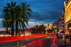 Personnes mobiles et bâtiments stables par la nuit Nice à l'ATF Image stock