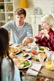 Personnes modernes dinant avec des amis à la maison Image libre de droits