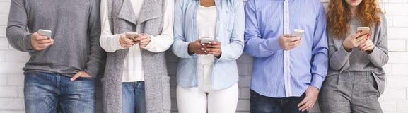 Personnes multi-ethniques jugeant des téléphones et la lecture rapide, se tenant dans la rangée photographie stock
