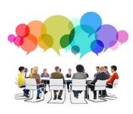 Personnes multi-ethniques lors d'une réunion avec des bulles de la parole Image stock