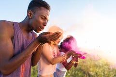 Personnes multi-ethniques soufflant la poudre colorée des paumes au festival de holi Images libres de droits