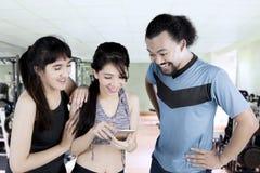 Personnes multiraciales avec le smartphone au gymnase Image stock