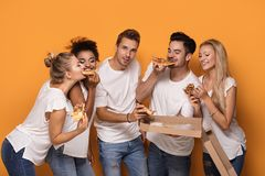 Personnes multiraciales ayant l'amusement, mangeant de la pizza Images libres de droits