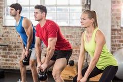 Personnes musculaires soulevant une cloche de bouilloire Image stock
