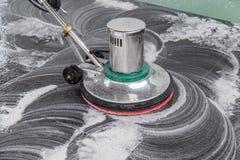 Personnes nettoyant le plancher noir de granit avec la machine et chimique thaïlandais Image libre de droits