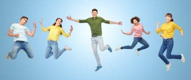 Personnes ou amis heureux sautant en air au-dessus de bleu Photo stock