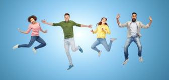 Personnes ou amis heureux sautant en air au-dessus de bleu Image stock