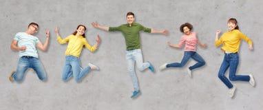 Personnes ou amis heureux sautant en air au-dessus de gris Photos stock