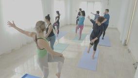 Personnes régulières avec de vrais corps pratiquant l'équilibre pendant une classe de yoga dans un studio de gymnase - banque de vidéos