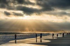 Personnes rétro-éclairées sur la plage au coucher du soleil, San Diego Image libre de droits