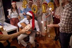 Personnes réussies de groupe d'affaires dans le chapeau de Santa à la partie de Noël célébrant avec la chanson photographie stock