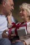 Personnes retraitées avec un cadeau Image stock