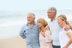 Personnes retraitées joyeuses marchant sur la plage Photos stock