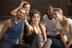 Personnes sportives multi-ethniques ayant l'amusement prenant le selfie de groupe dans le gymnase Image stock