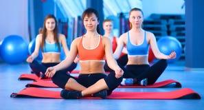 Personnes sportives s'asseyant sur des tapis d'exercice à un studio lumineux de forme physique Image stock