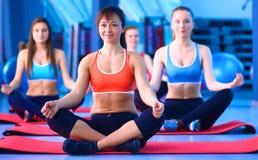 Personnes sportives s'asseyant sur des tapis d'exercice à un studio lumineux de forme physique Photo libre de droits