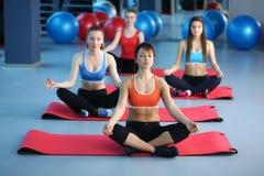 Personnes sportives s'asseyant sur des tapis d'exercice à un studio lumineux de forme physique Images libres de droits