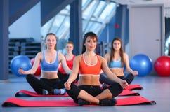 Personnes sportives s'asseyant sur des tapis d'exercice à un studio lumineux de forme physique Photographie stock