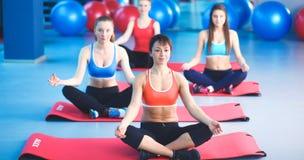 Personnes sportives s'asseyant sur des tapis d'exercice à un studio lumineux de forme physique Photo stock