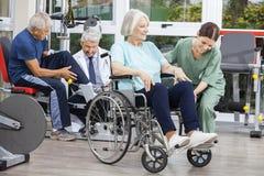 Personnes supérieures aidé par des physiothérapeutes au centre de réadaptation photographie stock
