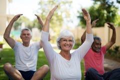 Personnes supérieures de sourire s'exerçant avec des bras augmentés Photographie stock