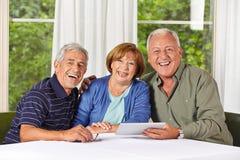 Personnes supérieures heureuses avec la tablette Photographie stock libre de droits